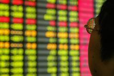 Китайский инвестор следит за ценами в Шанхае 12 ноября 2003 года. Объём торговли многими активами на финансовых рынках был ограничен в понедельник, так как инвесторы воздерживались от крупных ставок из-за геополитической напряжённости на Ближнем Востоке и Корейском полуострове.  REUTERS/Claro Cortes IV/File Photo