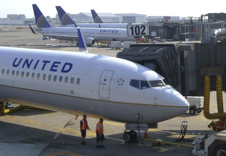 Two ground crew members walk past a United Airlines airplane as it sits at a gate at Newark Liberty International Airport in Newark, New Jersey, June 18, 2011.  REUTERS/Gary Hershorn