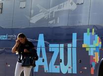 Mulher passa por ônibus decorado com logo da Azul no aeroporto de Viracopos, em Campinas. 11/04/2017 REUTERS/Paulo Whitaker