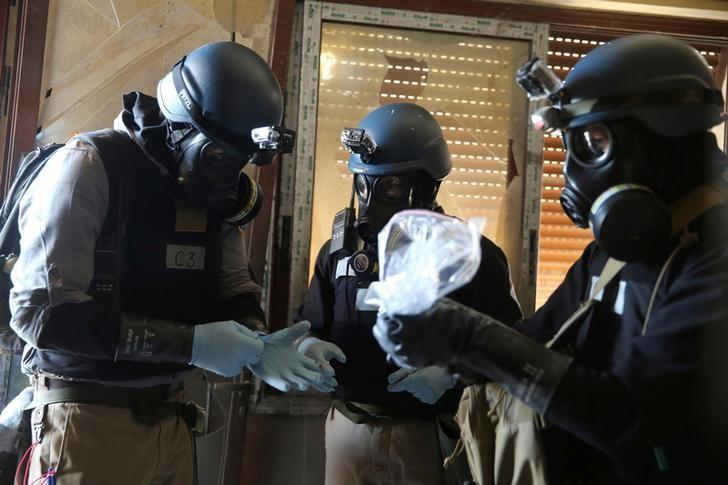 A U.N. chemical weapons expert, wearing a gas mask, holds a plastic bag containing samples from one of the sites of an alleged chemical weapons attack in the Ain Tarma neighbourhood of Damascus, Syria  August 29, 2013. REUTERS/Mohamed Abdullah/File Photo