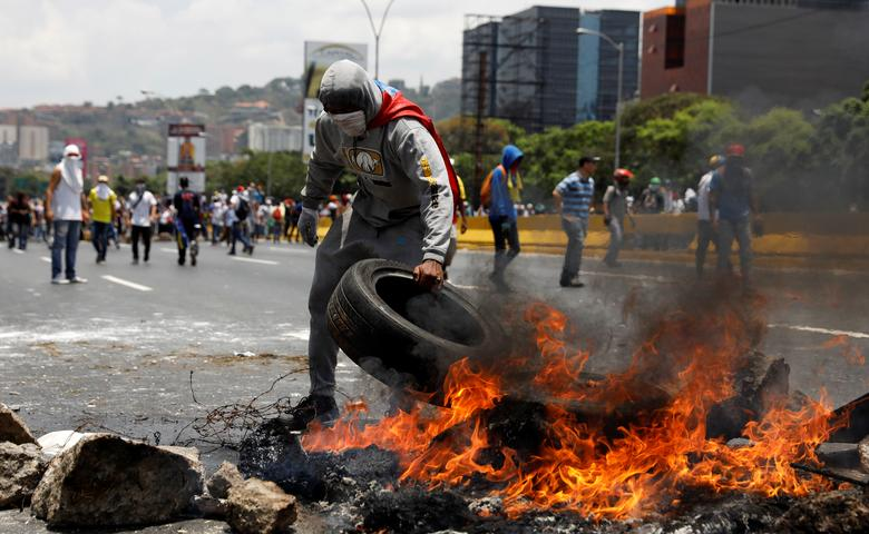 Demonstrators build a fire barricade on a street in Caracas. REUTERS/Carlos Garcia Rawlins