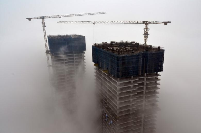 Buildings under construction are seen among fog in Rizhao, Shandong province, China, May 19, 2015. REUTERS/Stringer