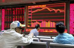 Investors chat in front of an electronic board showing stock information at a brokerage house in Beijing, China, September 16, 2015. China stocks ended up sharply on Wednesday helped by a spike in the final minutes of trade, a frequent phenomenon in mainland markets generally interpreted as government intervention to push up values before the closing bell. REUTERS/Stringer CHINA OUT. NO COMMERCIAL OR EDITORIAL SALES IN CHINA