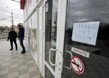 """Men stand near the front door of a shop on which an announcement (top R), which reads """"Closed, no power!"""", can be seen, in Simferopol, Crimea, November 22, 2015. A state of emergency has been declared in Crimea after pylons carrying electricity from Ukraine were blown up cutting off power to almost two million people, media and the Russian government said on Sunday. REUTERS/Pavel Rebrov"""