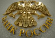 A coat of arms of the Russia's Central Bank is pictured in the bank's press room in Moscow, March 13, 2015. The Russian central bank cut its main lending rate on March 13, for the second time this year, putting concerns about the declining economy before worries about high inflation. REUTERS/Sergei Karpukhin (RUSSIA - Tags: BUSINESS LOGO)