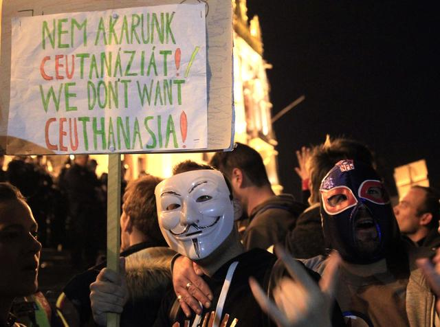 A man wearing Guy Fawkes mask holds placard as he protests in front of the Hungarian Parliament against a new law that would undermine Central European University, a liberal graduate school of social sciences founded by U.S. financier George Soros in Budapest, Hungary, April 12, 2016. REUTERS/Bernadett Szabo