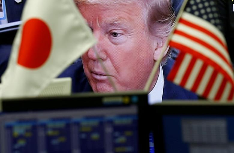 A TV monitor showing U.S. President Donald Trump is seen through national flags of the U.S. and Japan at a foreign exchange trading company in Tokyo, Japan February 1, 2017. REUTERS/Kim Kyung-Hoon