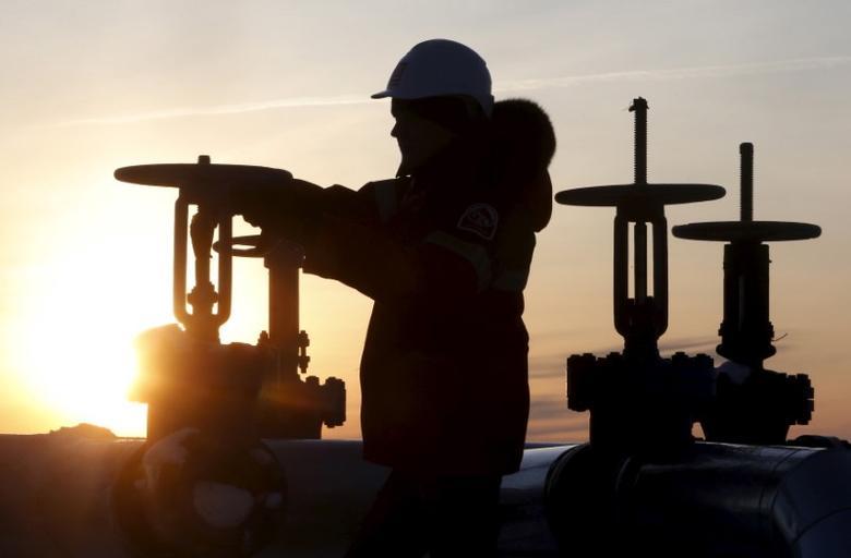 资料图片:2016年1月,俄罗斯西西伯利亚城市Kogalym外卢克公司旗下Imilorskoye油田的工人在检查油管阀门。REUTERS/Sergei Karpukhin