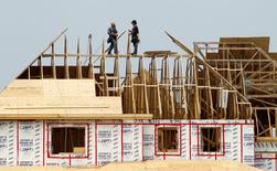 Builders work on the the roof of a new home under construction in the Montreal suburb of Brossard, August 10, 2010. REUTERS/Shaun Best
