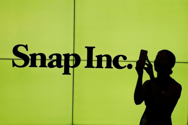 A woman stands in front of the logo of Snap Inc. on the floor of the New York Stock Exchange (NYSE) while waiting for Snap Inc. to post their IPO, in New York City, NY, U.S. March 2, 2017. REUTERS/Lucas Jackson/Files