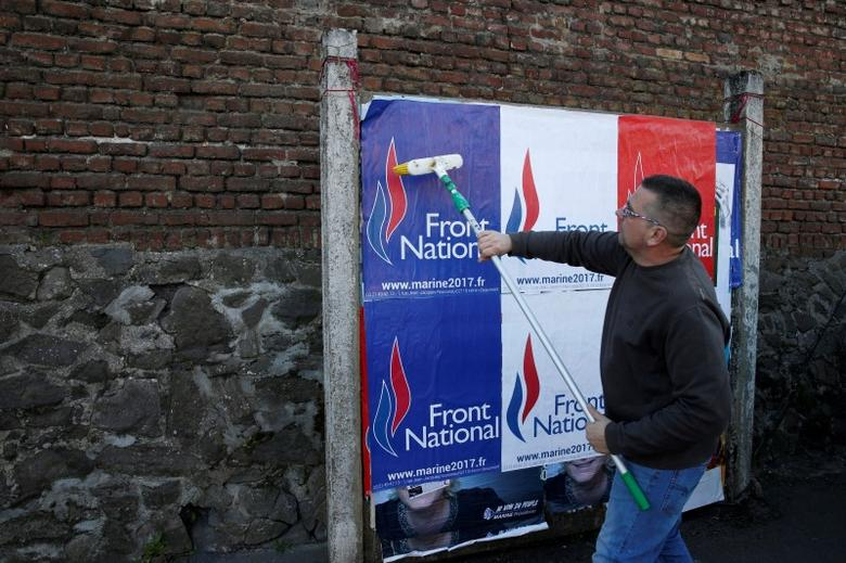 Emmanuel Rignaux, a member of the National Front party, pastes a poster on a free billboard for French far right National Front political party leader Marine Le Pen as part of the 2017 French presidential election campaign in Henin-Beaumont, France, April 6, 2017. Picture taken April 6, 2017.  REUTERS/Pascal Rossignol