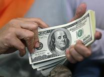 Женщина держит в руках долларовые купюры в пункте обмена валюты в Джакарте 13 июня 2012 года. Доллар нёс потери в пятницу и готовился к недельному спаду, так как сохранение напряжённости в Северной Корее поддерживало японскую иену, считающуюся безопасным активом.  REUTERS/Beawiharta