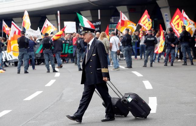 4月14日、イタリアの航空大手アリタリア航空と労働組合は、事業継続のために人員削減と賃金カットで暫定合意に至ったと発表した。写真はローマのフィウミチーノ国際空港でストに参加するアリタリア航空の職員らと、通り過ぎるパイロット。5日撮影(2017年 ロイター/Remo Casilli)