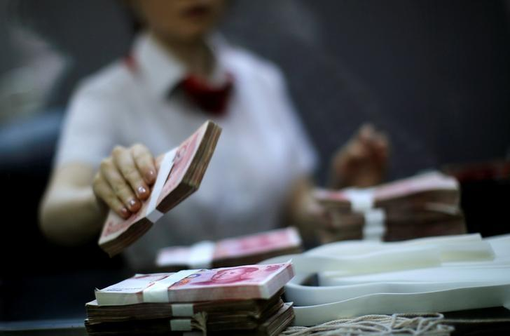 FILE PHOTO: An employee of the Industrial and Commercial Bank of China Ltd (ICBC) counts money at one of the bank's branches at the Shanghai Free Trade Zone in Pudong district, in Shanghai September 24, 2014. REUTERS/Carlos Barria/File Photo