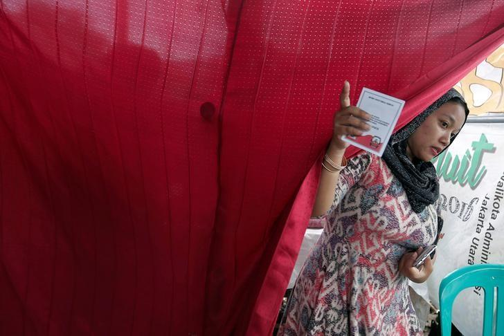 An Indonesian woman holds a paper after casting her ballot during an election for Jakarta's governor in Jakarta, Indonesia, February 15, 2017. REUTERS/Beawiharta