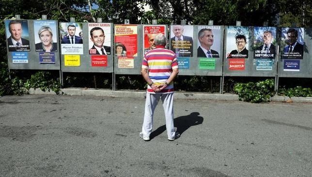 4月13日、約2週間後に第1回投票が迫ったフランス大統領選は、候補者4人が入り乱れる大混戦となっている。候補者のポスターを眺める男性。ニース近郊で10日撮影(2017年 ロイター/Eric Gaillard)
