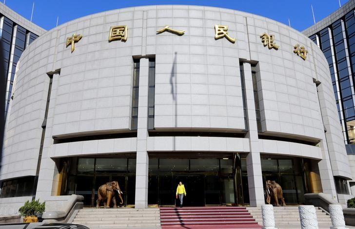 FILE PHOTO: A woman walks out of the headquarters of the People's Bank of China (PBOC), the central bank, in Beijing November 20, 2013.  REUTERS/Jason Lee/File Photo