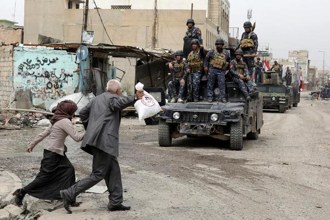 4月16日、イラクの警察当局は過激派組織「イスラム国」(IS)が北部モスルでの戦闘で化学兵器を使用したとして非難した。だが、これにより軍の進めるモスル西部奪還作戦が妨げられることはないという。写真はモスル西部をパトロールするイラクの警察部隊と励ましの声をかける市民(2017年 ロイター/Marko Djurica)