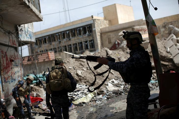 A member of the Iraqi Federal Police takes his rifle to hang it on his shoulder in an area controlled by Iraqi forces fighting the Islamic State in western Mosul, Iraq, April 12, 2017. REUTERS/Andres Martinez Casares/Files