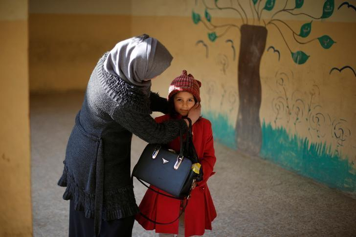 A mother adjusts her daughter's hat before she enters a classroom in school in Mosul, Iraq, January 23, 2017. REUTERS/Muhammad Hamed/Files