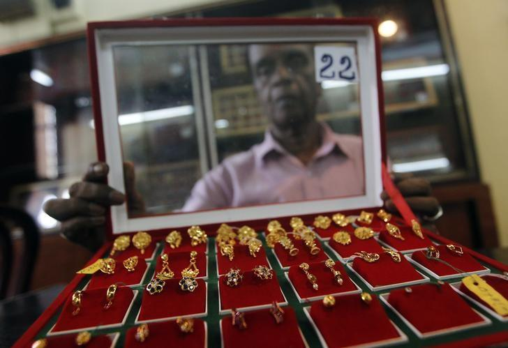 A vendor shows gold stud earrings to a customer at a jewellery showroom in Colombo December 2, 2013. REUTERS/Dinuka Liyanawatte