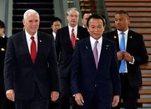 U.S. Vice President Mike Pence (L) and Japan's Deputy Prime Minister Taro Aso walk on their way to a meeting at Prime Minister Shinzo Abe's (not pictured) official residence in Tokyo, Japan April 18, 2017.  REUTERS/Franck Robichon/Pool