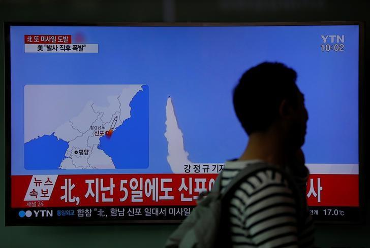 A passenger walks past a TV broadcasting a news report on North Korea's failed missile launch from its east coast, at a railway station in Seoul, South Korea, April 16, 2017.   REUTERS/Kim Hong-Ji