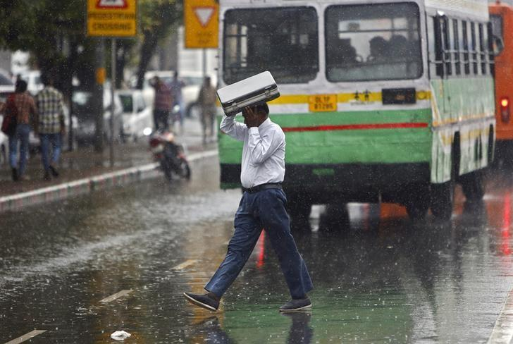 A commuter uses his briefcase to protect himself from rain in New Delhi, India, August 7, 2015. REUTERS/Anindito Mukherjee/Files