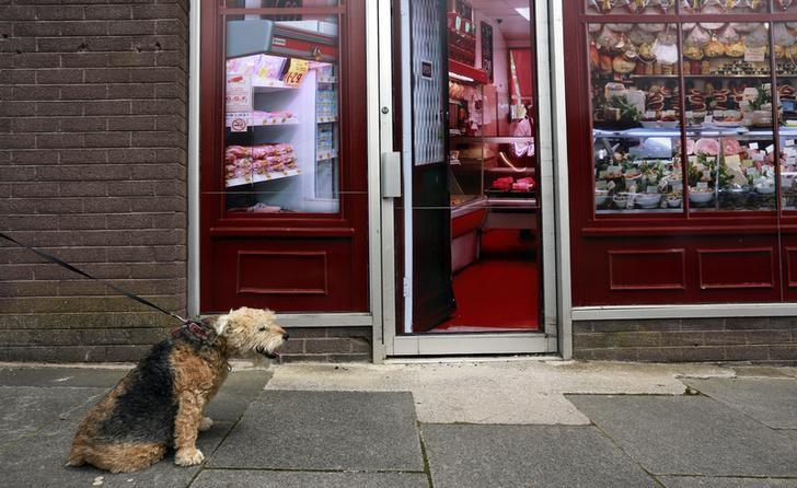 A man walks his dog past a vacant shop, with graphics pasted to the outside to make it look like working butchers shop, in the village of Belcoo, Northern Ireland June 3, 2013.  REUTERS/Cathal McNaughton/Files