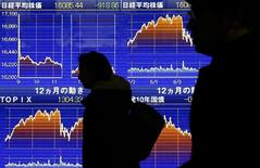 Pedestrians walk past an electronic board showing the graphs of the recent fluctuations of Japan's Nikkei average outside a brokerage in Tokyo, Japan, February 9, 2016. A drop in bank shares kept European shares under pressure on Tuesday, after losses in Asian markets sent investors scurrying for safe havens. REUTERS/Yuya Shino