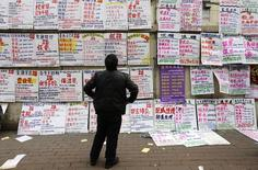 A man looks at job information at an employment fair beside a street in Zhengzhou, Henan province, February 19, 2014. REUTERS/Jason Lee (CHINA - Tags: SOCIETY BUSINESS EMPLOYMENT)