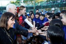 El vicepresidente de Estados Unidos, Mike Pence, y su esposa Karen saludan a las integrantes de un equipo de softball en Tokio.  Abril 19, 2017. REUTERS/Kim Kyung-Hoon
