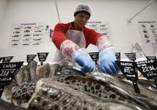 An employee arranges fresh fish at a grocery store which is the 100th store of French retail group Auchan opened in the country, in Moscow, Russia, December 13, 2016.  REUTERS/Maxim Shemetov