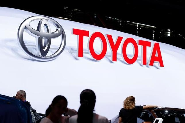 The logo of Japanese car manufacturer Toyota is displayed behind members of the media at the Paris auto show, in Paris, France, September 29, 2016.   REUTERS/Benoit Tessier/Files