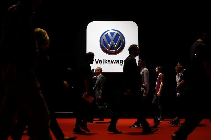 People pass in front of a Volkswagen logo at Shanghai Auto Show during its media day, in Shanghai, China April 19, 2017. REUTERS/Aly Song