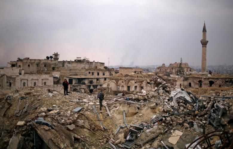 File photo: A member of forces loyal to Syria's President Bashar al-Assad stands with a civilian on the rubble of the Carlton Hotel, in the government controlled area of Aleppo, Syria December 17, 2016. REUTERS/Omar Sanadiki
