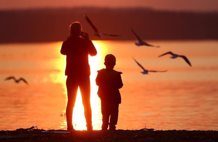 2017年4月2日,明斯克郊区,一名女子在湖边拍摄夕阳美景。REUTERS/Vasily Fedosenko
