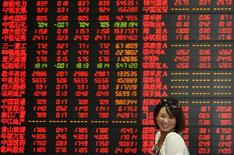 """An investor smiles as she walks past an electronic board showing stock information at a brokerage house in Fuyang, Anhui province, China, July 17, 2015. China stocks closed up on Friday, overcoming a mid-week slide to end up for a second week, with market insiders saying the """"national team"""" of brokerages, mutual funds and market regulators were intensifying intervention, especially in the futures market. REUTERS/Stringer CHINA OUT. NO COMMERCIAL OR EDITORIAL SALES IN CHINA"""