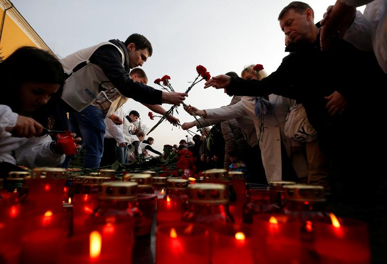 FILE PHOTO: People lay flowers during a memorial to pay tribute to the victims of the St. Petersburg metro blast that took place on April 3, in central Moscow, Russia April 6, 2017. REUTERS/Maxim Shemetov