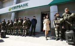 Военнослужащие Нацгвардии Украины у отделения Сбербанка в Киеве 10 апреля 2017 года. Глава государственного Сбербанка Герман Греф сказал, что продажа дочернего банка на Украине не предполагает безденежный характер сделки. REUTERS/Gleb Garanich