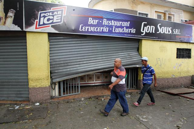 People walk past the damaged entrance of a restaurant after it was looted in Caracas, Venezuela April 20, 2017. REUTERS/Christian Veron