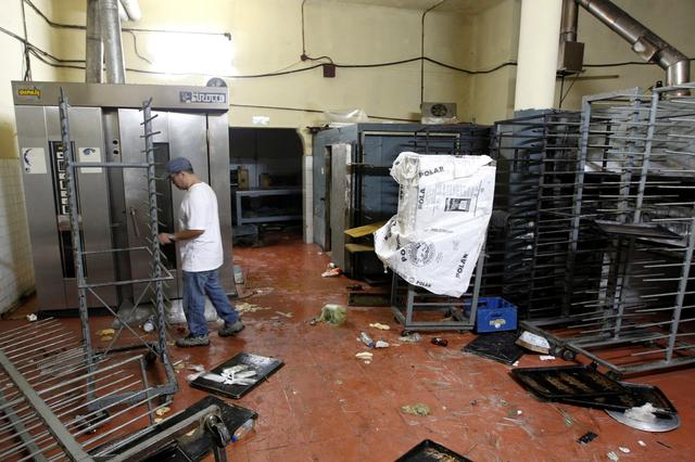 A worker walks next to damaged goods and empty shelves in a bakery, after it was looted in Caracas, Venezuela April 20, 2017. REUTERS/Christian Veron