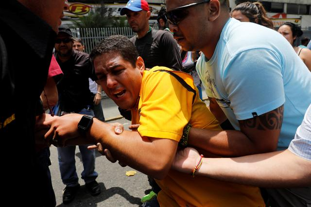 Deputy of the opposition party Justice First (Primero Justicia) Jose Olivares (C) reacts after he was affected by tear gas during a rally against Venezuela's President Nicolas Maduro in Caracas, Venezuela, April 20, 2017. REUTERS/Carlos Garcia Rawlins