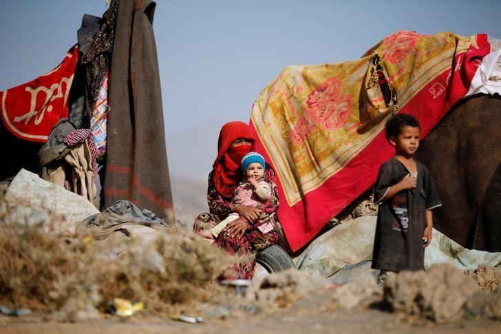 A woman sits with her children near their tent at a camp for internally displaced people in Dharawan, near the capital Sanaa, Yemen February 28, 2017. REUTERS/Khaled Abdullah