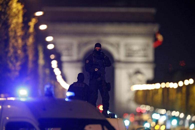 Masked police stand on top of their vehicle on the Champs Elysees Avenue after a shooting incident in Paris, France, April 20, 2017. REUTERS/Christian Hartmann