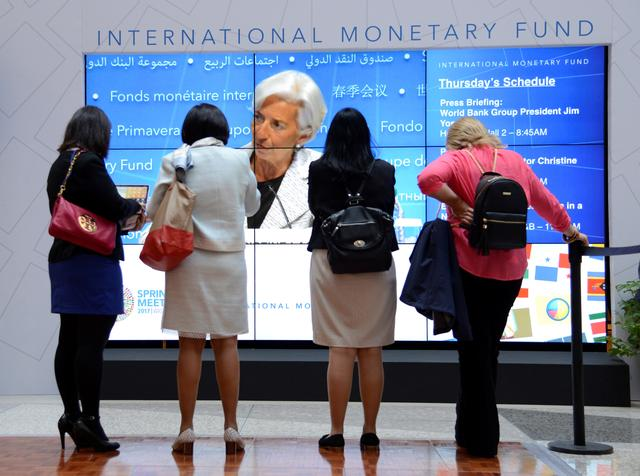 Visitors listen to remarks by IMF Managing Director Christine Lagarde on a giant monitor in the atrium of the IMF headquarters during a press briefing to open the IMF and World Bank's 2017 Annual Spring Meetings, in Washington, U.S., April 20, 2017.   REUTERS/Mike Theiler