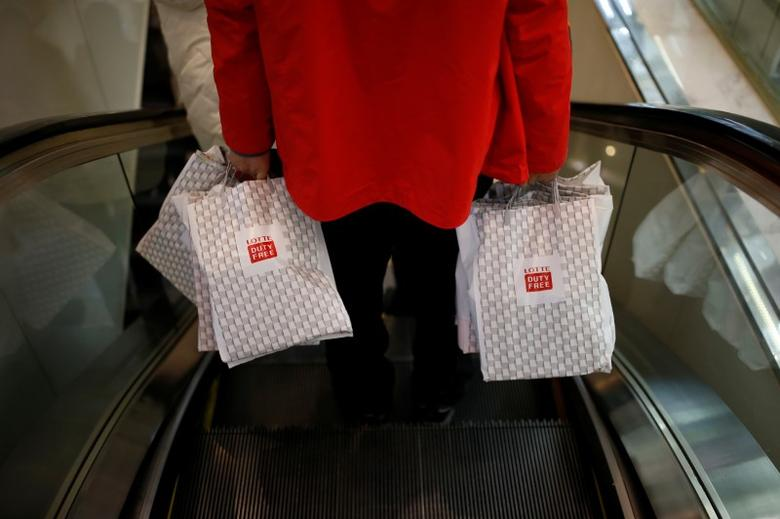 A man carryng his shopping bags rides on an escalator at a Lotte duty free shop in Seoul, South Korea, December 13, 2016. Picture taken December 13, 2016.  REUTERS/Kim Hong-Ji