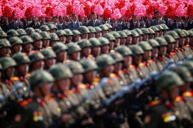People hold plastic flowers behind North Korean soldiers marching during a military parade marking the 105th birth anniversary of the country's founding father, Kim Il Sung in Pyongyang, North Korea April 15, 2017.    REUTERS/Damir Sagolj