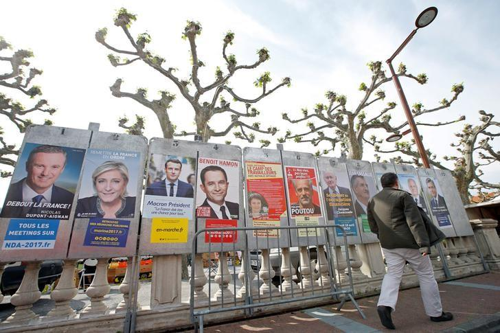 A man walks past campaign posters of the 11 candidates who run in the 2017 French presidential election in Le Soler, near Perpignan, France April 15, 2017. (L-R) Debout La France group candidate Nicolas Dupont-Aignan, French National Front (FN) political party leader Marine Le Pen, head of the political movement En Marche! (Onwards!) Emmanuel Macron, French Socialist party candidate Benoit Hamon, France's extreme-left Lutte Ouvriere political party (LO) leader Nathalie Arthaud, Anti-Capitalist Party (NPA) presidential candidate Philippe Poutou, ''Solidarite et Progres'' (Solidarity and Progress) party candidate Jacques Cheminade, lawmaker and independent candidate Jean Lassalle, candidate of the French far-left Parti de Gauche Jean-Luc Melenchon, UPR candidate Francois Asselineau and the Republicans political party candidate Francois Fillon. REUTERS/Jean-Paul Pelissier - RTS12EHB