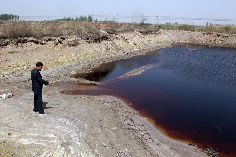 A villager stands on land polluted by industrial wastewater in Langfang, Hebei province, China April 20, 2017. Picture taken April 20, 2017. REUTERS/Stringer